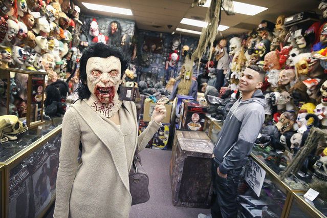 Iris Chavez (L) and Tony Monroe shop for Halloween costumes at Fantasy Costumes on October 28, 2014 in Chicago, Illinois. With about a third of the population either attending or throwing Halloween parties, Americans are expected to spend $7.4 billion on the holiday this year. Fantasy Costumes will stay open 24 hours-a-day from October 24 until October 31. (Photo by Scott Olson/Getty Images)