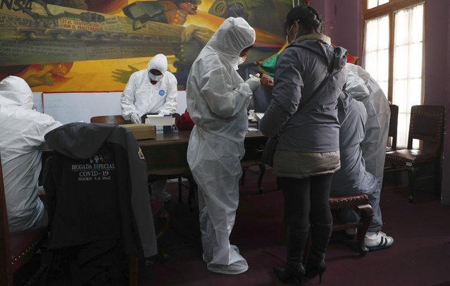 Healthcare workers dressed in full protective gear test journalists for the new coronavirus at a trade union office for media workers, in La Paz, Bolivia, Wednesday, August 19, 2020. Journalists asked the government to provide free rapid tests because many are worried after learning that several of their colleagues have been infected with COVID-19. (Photo by Juan Karita/AP Photo)