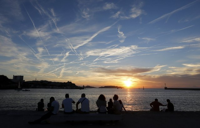 Clouds fill the sky as people watch the setting sun at on a warm autumn day in Marseille October 18, 2014. (Photo by Jean-Paul Pelissier/Reuters)