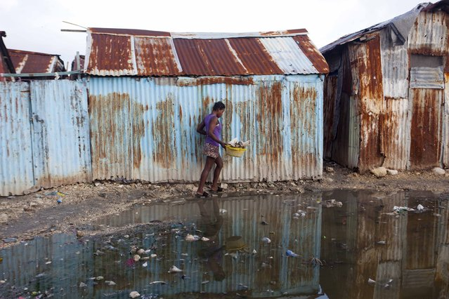 A woman skirts a puddle as she walks home in the seaside slum of Port-au-Prince, Haiti, Wednesday, September 6, 2017. Heavy rain and 185-mph winds lashed the Virgin Islands and Puerto Rico's northeast coast Wednesday as Hurricane Irma roared through Caribbean islands. The northern parts of the Dominican Republic and Haiti could see 10 inches of rain. (Photo by Dieu Nalio Chery/AP Photo)