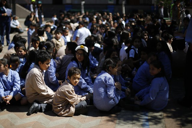 Students gather in a playground at a school during an earthquake drill in Santiago, November 13, 2014. (Photo by Ivan Alvarado/Reuters)