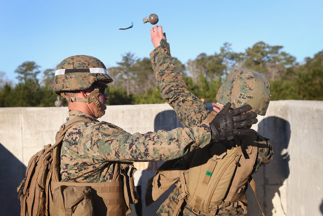Sgt. Daniel Pettway (L) of Jacksonville, NC instructs Pfc. Shaina Hart of Floydada, TX the proper technique for throwing a hand grenade during Marine Combat Training (MCT) on February 21, 2013 at Camp Lejeune, North Carolina.  Since 1988 all non-infantry enlisted male Marines have been required to complete 29 days of basic combat skills training at MCT after graduating from boot camp. MCT has been required for all enlisted female Marines since 1997. About six percent of enlisted Marines are female.  (Photo by Scott Olson)