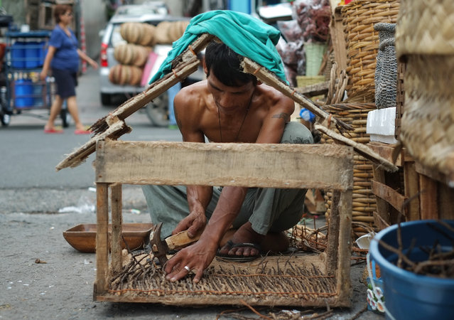 Filipino Victor Albano, 39, works on a small nativity house which he would sell for 500 peso ($11) at his makeshift stall as people begin shopping for Christmas decorations in Manila, Philippines, Thursday, November 20, 2014. Christmas is one of the most important holidays in this predominantly Roman Catholic nation. Albano said he sometimes take home about 700 peso ($16) a day during this season. (Photo by Aaron Favila/AP Photo)
