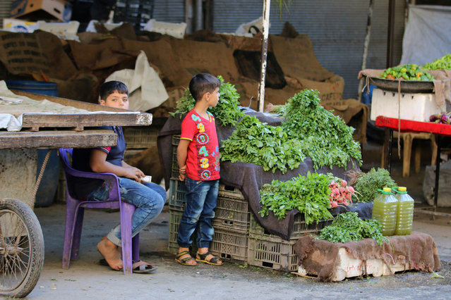 Boys stand near a vegetable stand inside a market in the rebel-held al-Shaar neighbourhood of Aleppo, Syria, September 17, 2016. (Photo by Abdalrhman Ismail/Reuters)