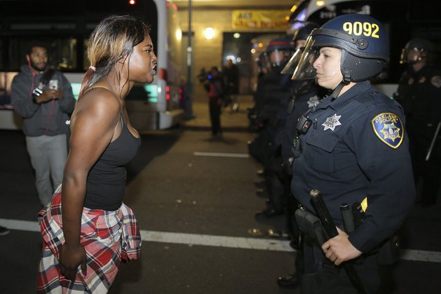 Amanda Ashe of Oakland, left, faces off with a police officer during the second night of demonstrations in Emeryville, California, following the grand jury decision in the shooting of Michael Brown in Ferguson, Missouri, November 25, 2014. (Photo by Elijah Nouvelage/Reuters)