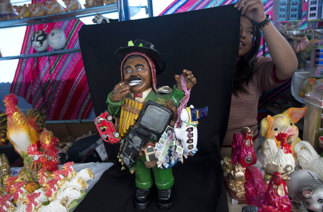 "In this February 20, 2018 photo, fair vendor Noelia Flores holds up a black backdrop behind a small statue of an ""Ekeko"", the god of prosperity, for a portrait at her booth during the annual Alasita Fair in La Paz, Bolivia. Every year, thousands of Bolivians head to the feast of Alasitas that is held in his honor to buy miniature cars, houses and toy dollar bills symbolizing their dreams of prosperity. (Photo by Juan Karita/AP Photo)"
