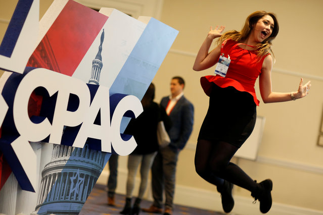 Elizabeth Mills jumps in front of the Conservative Political Action Conference (CPAC) sign at National Harbor, Md., February 23, 2018. (Photo by Joshua Roberts/Reuters)