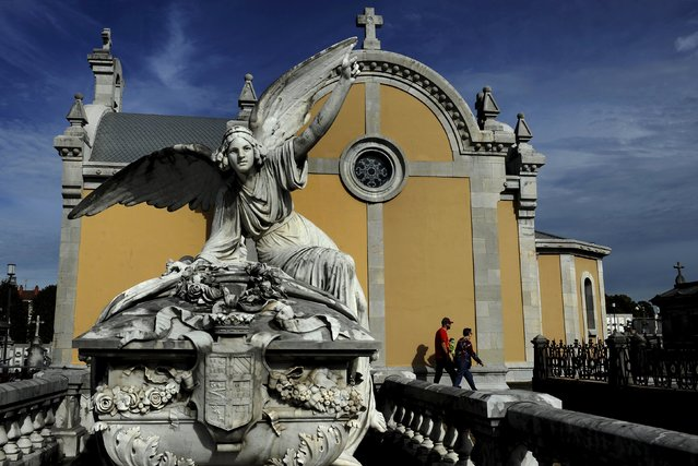 People walk next to of the pantheon of the Marquesa de San Juan de Nieva, chosen as the best tomb sculpture of Spain in a Spanish magazine this week, in the municipal cemetery of La Carriona in Aviles, northern Spain, October 29, 2015. (Photo by Eloy Alonso/Reuters)