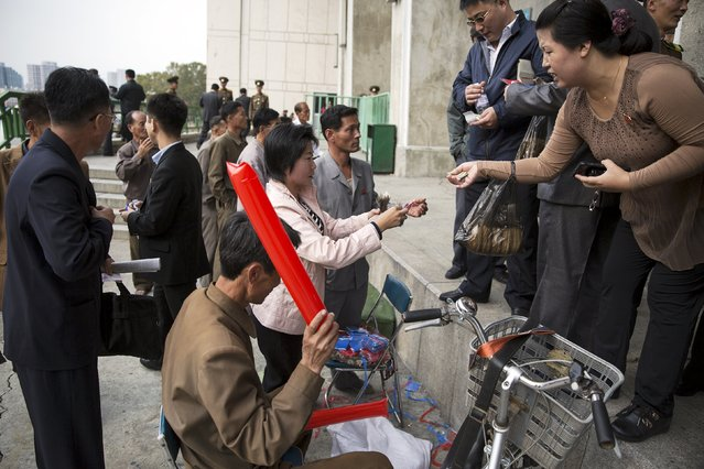 People use North Korean won and U.S. dollars to buy inflatable clappers at a black market exchange rate before a football match at the Kim Il Sung Stadium in Pyongyang October 8, 2015. (Photo by Damir Sagolj/Reuters)