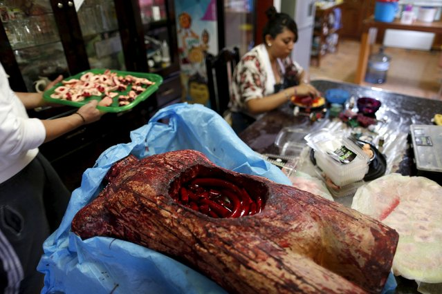 A bloody, fake open torso with jelly guts made of gummy candy is seen as a woman works at the Zombie Gourmet homemade candy manufacturer on the outskirts of Mexico City October 30, 2015. (Photo by Carlos Jasso/Reuters)