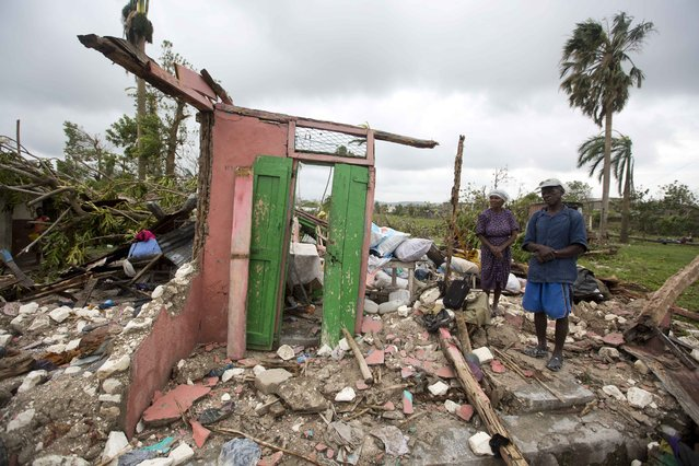 Saintanor Dutervil stands with his wife in the ruins of their home destroyed by Hurricane Matthew in Les Cayes, Haiti, Thursday, October 6, 2016. Two days after the storm rampaged across the country's remote southwestern peninsula, authorities and aid workers still lack a clear picture of what they fear is the country's biggest disaster in years. (Photo by Dieu Nalio Chery/AP Photo)