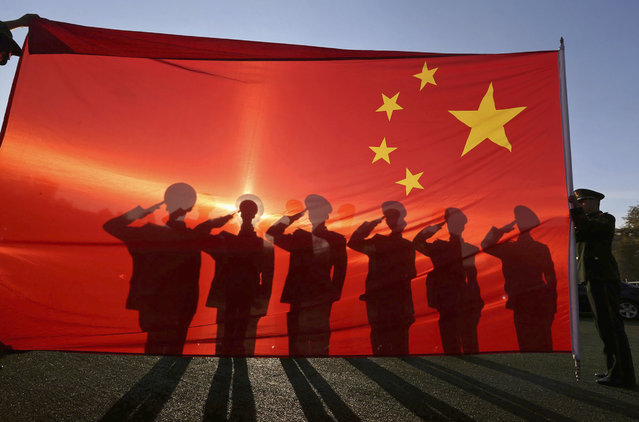 Retired paramilitary policemen, who conduct the daily national flag raising and lowering ceremony on Tiananmen Square, salute to a Chinese national flag during a farewell ceremony in Beijing, November 24, 2014. (Photo by Reuters/Stringer)