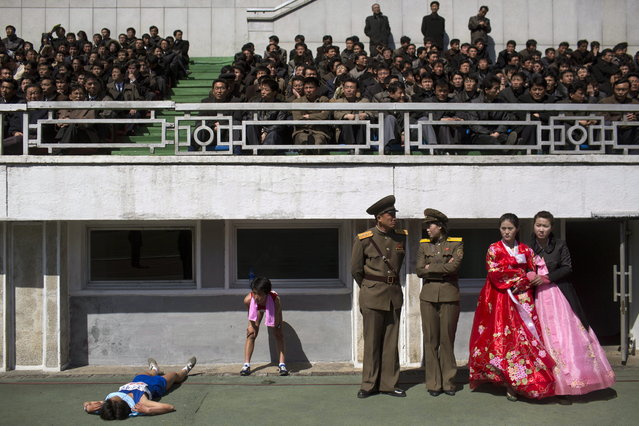 Runners rest inside Kim Il Sung Stadium in Pyongyang, North Korea on Sunday, April 14, 2013. North Korea hosted the 26th Mangyongdae Prize Marathon to mark the upcoming April 15, 2013 birthday of the late leader Kim Il Sung. (Photo by Alexander F. Yuan/AP Photo)