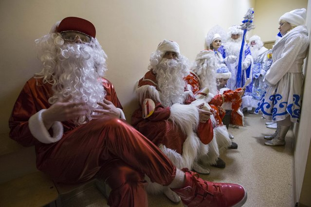 "People dressed as Father Frost, the equivalent of Santa Claus, and Snow Maiden wait to take part in the contest ""Yolka-fest-2014"" (Fir-festival-2014) in Minsk December 12, 2014. (Photo by Vasily Fedosenko/Reuters)"