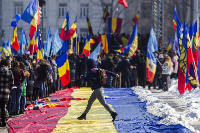A girl jumps across a large Romanian flag during a rally to mark the 100th anniversary of the unification of Moldova with Romania, in the Great National Assembly Square in Chisinau, Moldova, 25 March 2018. The National Council of the Republic of Moldova declared the country's independence on 02 December 1917. The Unification with Romania happened on 27 March 1918. (Photo by Dumitru Doru/EPA/EFE)