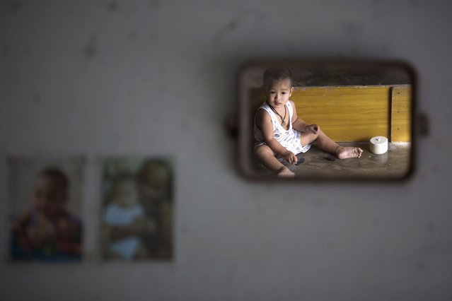 A child is reflected in a mirror at barber's home in Ban Nam Khem, December 13, 2014. Therasak, a local barber who survived 2004 tsunami with his family members, returned to the village soon after disaster but says his 22 year old daughter still suffers from tsunami related illness. (Photo by Damir Sagolj/Reuters)