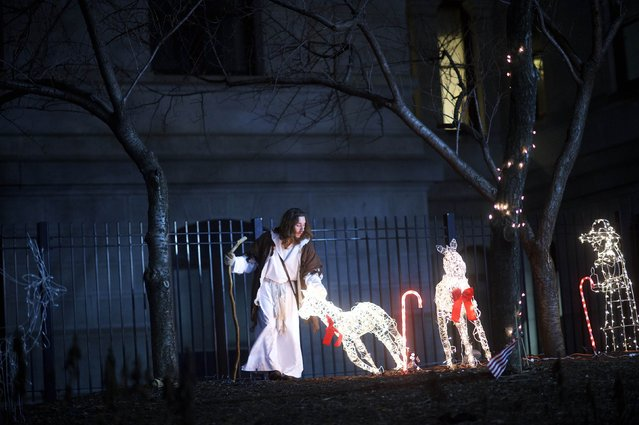 "Michael Grant, 28, ""Philly Jesus"", lifts a fallen Christmas decoration in the courtyard of Philadelphia City Hall in Philadelphia, Pennsylvania December 14, 2014. (Photo by Mark Makela/Reuters)"