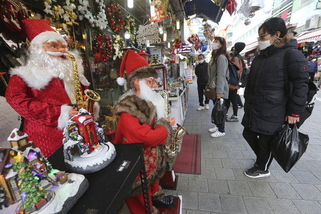 People wearing face masks as a precaution against the coronavirus watch Christmas decorations at a store in Seoul, South Korea, Friday, November 27, 2020. South Korea's daily virus tally hovered above 500 for the second straight day, as the country's prime minister urged the public to stay home this weekend to contain a viral resurgence. (Photo by Ahn Young-joon/AP Photo)