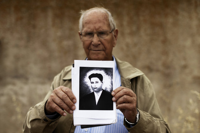 In this photo taken on July 19, 2014, Camilo De Dios, 81, stands in front of the wall in Chaherrero, Spain, where his brother Perfecto de Dios was killed at the age of 19, holding Perfecto's only portrait. (Photo by Daniel Ochoa de Olza/AP Photo)