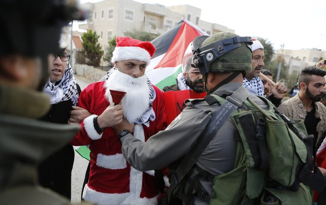 A Palestinian protester dressed in a Santa Claus costume argues with an Israeli border policeman during a demonstration against the Israeli settlements and demanding for free movement for the Palestinians during Christmas near a checkpoint in the West Bank city of Bethlehem December 23, 2014. (Photo by Mussa Qawasma/Reuters)