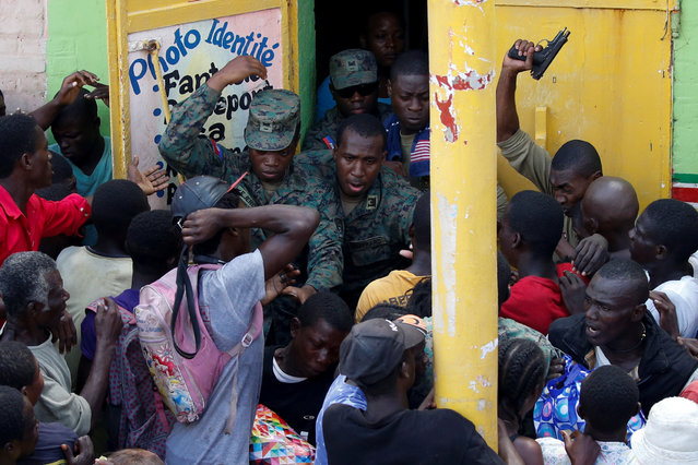 Haitian soldiers shoot in the air to try to control the crowd as they wait for food to be handed out after Hurricane Matthew hit Jeremie, Haiti, October 18, 2016. (Photo by Carlos Garcia Rawlins/Reuters)
