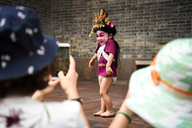 Visitors take photos of a child dressed in a traditional costume before a folk performance in Panyu, Guangdong province, China on April 20, 2018. (Photo by Reuters/China Daily)