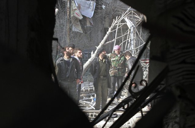 Men inspect a site hit by what activists said was an air strike by forces loyal to Syria's President Bashar al-Assad in the Duma neighbourhood of Damascus December 27, 2014. (Photo by Reuters/Stringer)