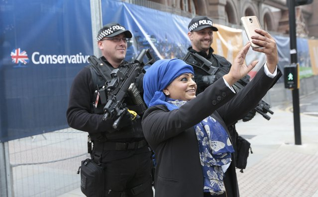 A woman poses for a selfie with two armed police guards at the entrance of the Conservative Party Conference in Manchester, Britain October 4, 2015. (Photo by Suzanne Plunkett/Reuters)
