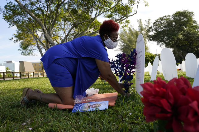 """Sheila Roberts, 61, leaves flowers for her mother Lula M. Hunter-Roberts, who recently died at age 87 of COVID-19, at a symbolic cemetery created to remember and honor lives lost to the virus, Tuesday, December 15, 2020, in the Liberty City neighborhood of Miami. Roberts said her mother was a beautiful spirit inside and out, and that """"she shined bright like a diamond"""". (Photo by Lynne Sladky/AP Photo)"""