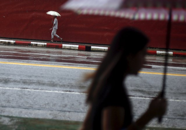 People use umbrellas during rain fall as they walk down a road in Yangon, Myanmar September 18, 2015. (Photo by Soe Zeya Tun/Reuters)