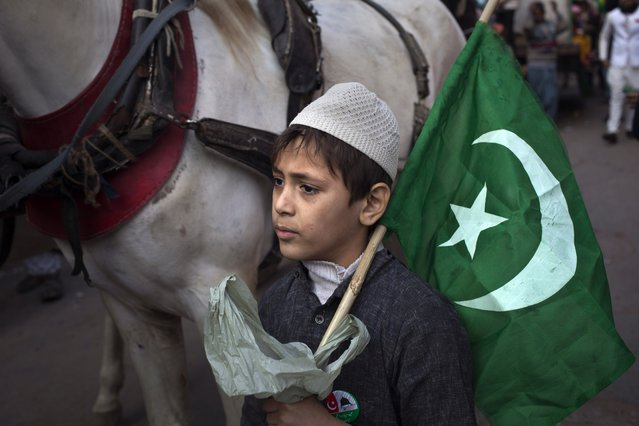 An Indian Muslim boy carries a religious flag during a religious procession to mark the birth anniversary of Prophet Mohammad at old quarters of New Delhi, India, Sunday, January 4, 2015. (Photo by Tsering Topgyal/AP Photo)