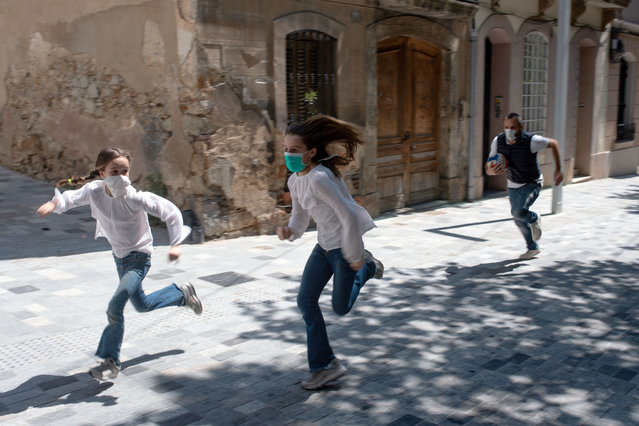 Joan, 45, chases his daughters Ines, 11, and Mar, 9, as they play in the street on April 26, 2020, in Barcelona, during a national lockdown to prevent the spread of the COVID-19 disease. After six weeks stuck at home, Spain's children were being allowed out today to run, play or go for a walk as the government eased one of the world's toughest coronavirus lockdowns. Spain is one of the hardest hit countries, with a death toll running a more than 23,000 to put it behind only the United States and Italy despite stringent restrictions imposed from March 14, including keeping all children indoors. (Photo by Josep Lago/AFP Photo)