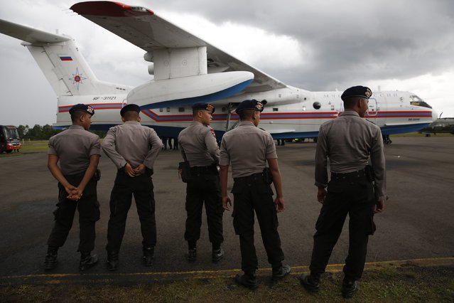 Indonesian police stand near a Beriev Be-200 amphibious plane carrying equipment for Russian rescue teams searching for AirAsia QZ8501 at the airbase in Pangkalan Bun, Central Kalimantan January 4, 2015. A multinational team searching for a crashed AirAsia passenger jet found another large underwater object believed to be part of the plane. (Photo by Darren Whiteside/Reuters)
