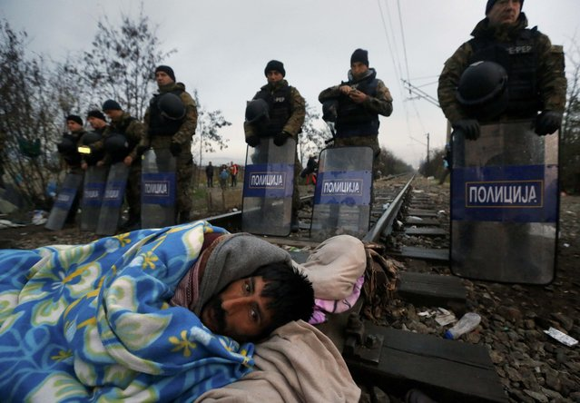 A stranded Iranian migrant on hunger strike weaks-up in front of Macedonian riot police at the borderline between Greece and Macedonia, near the Greek village of Idomeni November 25, 2015. European countries are stretched to their limits in the refugee crisis and cannot take in any more new arrivals, the French Prime Minister was quoted as saying in a German newspaper on Wednesday. (Photo by Yannis Behrakis/Reuters)