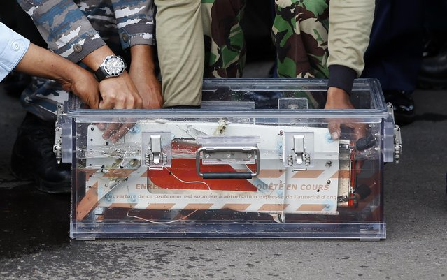 The flight data recorder from AirAsia QZ8501 is placed into a container upon its arrival at the airbase in Pangkalan Bun, Central Kalimantan January 12, 2015. (Photo by Darren Whiteside/Reuters)