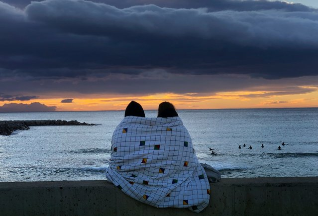 A couple watch the sunrise in front of the Mediterranean Sea in Barcelona, Spain, Sunday, January 24, 2021. (Photo by Emilio Morenatti/AP Photo)