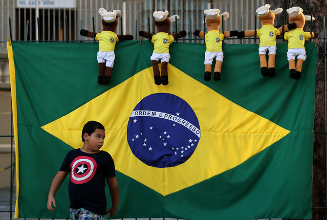 A Brazilian flag and dolls for sale are seen as a boy walks ahead of the 2018 World Cup, in Rio de Janeiro, Brazil June 13, 2018. (Photo by Sergio Moraes/Reuters)
