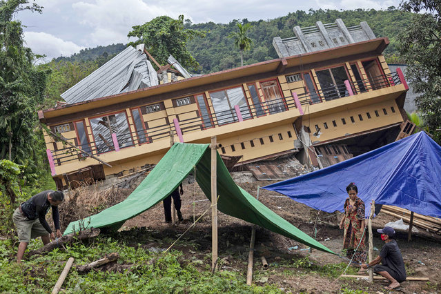 Residents build tents outside their house badly damaged by earthquake in Mamuju, West Sulawesi, Indonesia, Tuesday, January 19, 2021. Aid was reaching the thousands of people left homeless and struggling after an earthquake that killed a number of people struck early Friday. (Photo by Yusuf Wahil/AP Photo)