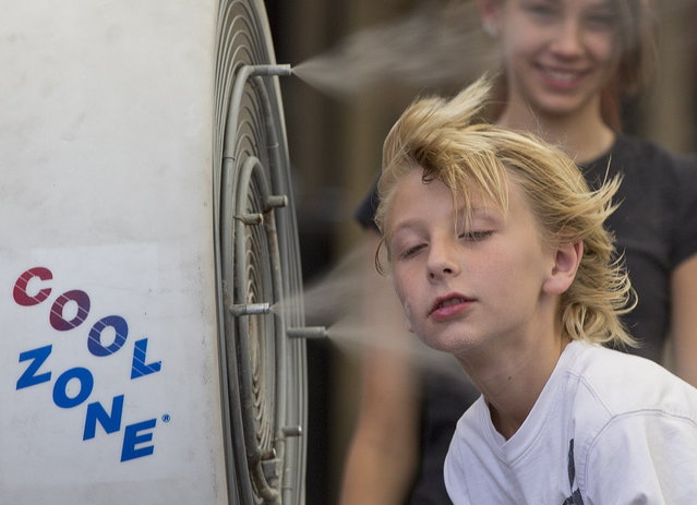 Ten-year-old Easton Martin, of Mesa, Ariz., stops to cool off in a misting fan while walking along The Strip with his family, Friday, June 28, 2013 in Las Vegas. A blazing heat wave expected to send the mercury soaring to nearly 120 degrees in Phoenix and Las Vegas settled over the West on Friday, threatening to ground airliners and raising fears that people and pets will get burned on the scalding pavement. (Photo by Julie Jacobson/AP Photo)