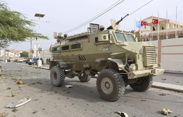 Soldiers from the African Union Mission in Somalia (AMISOM) drive their armoured personnel carrier (APC) past the scene of a suicide car explosion in front of the SYL hotel in the capital Mogadishu January 22, 2015. The Somali Islamist group al Shabaab claimed responsibility for a bomb attack at the gate of the hotel where Turkish delegates were meeting on Thursday, a day ahead of a visit by their president, Tayyip Erdogan, to the Somali capital. (Photo by Feisal Omar/Reuters)