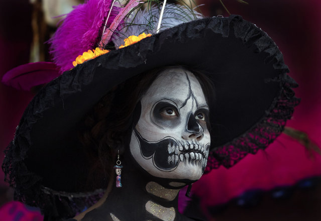 "Tonantzin Guerrero is dressed as a ""Catrina"" to perform in a play promoting the upcoming Day of the Dead holiday, in the Xochimilco borough of Mexico City, Friday, October 23, 2020. The iconic figures of skeletons with elegant wide-brimmed hats better known as Catrinas were created as satirical prints by Mexican artist Jose Guadalupe Posada sometime between 1910 and his death in 1913. (Photo by Marco Ugarte/AP Photo)"