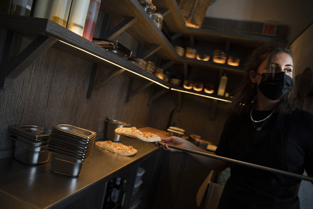 A member of staff prepares to put a pizzette into an oven as she prepares take-away orders at Sergio Herman's Le Pristine restaurant in Antwerp, Belgium, Friday, November 6, 2020. Of all the many challenges the pandemic throws up for all kinds of professions, this one has been particularly tough: How to put a three-star chef into a takeout box. (Photo by Virginia Mayo/AP Photo)