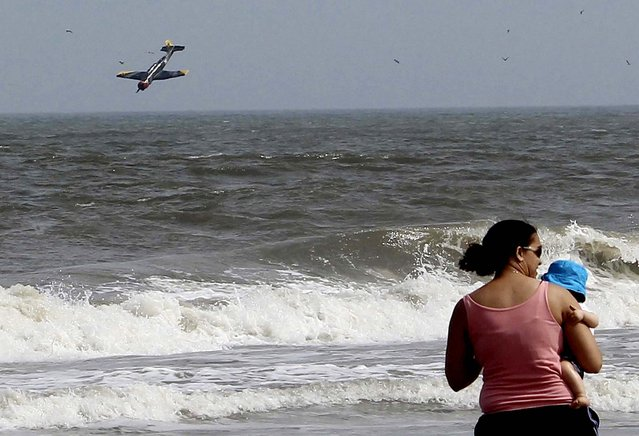 In this photo released on July 1, 2013, a woman holds her child as a plane crashes into the Atlantic Ocean with two off-duty police officers, off Ocean City, Maryland on Sunday. Troopers say the plane took off from the Ocean City Municipal Airport between 3:30 p.m. and 3:45 p.m. Sunday. Maryland State Police identified the men as 27-year-old Joshua D. Adickes of Berlin and 43-year-old Thomas J. Geoghegan Jr. of Ocean City. Both men were officers with the Ocean City Police Department. (Photo by Lisa Rufo/Associated Press)