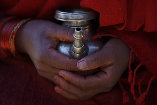 A devotee holds a vessel filled with holy water during the Swasthani Bratakatha festival in Panauti near Kathmandu January 24, 2015. (Photo by Navesh Chitrakar/Reuters)