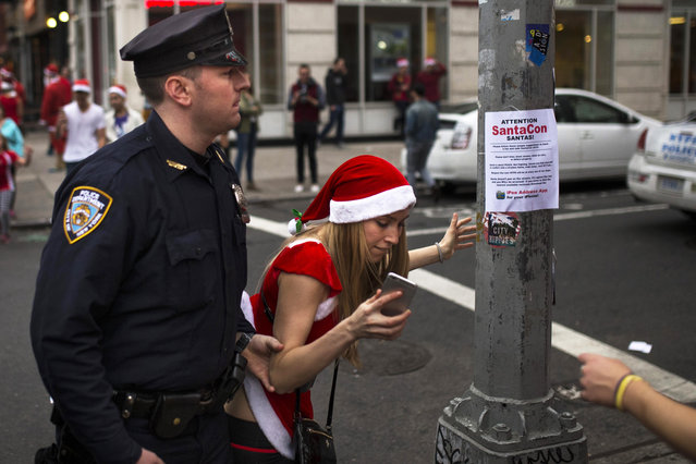 A police officer removes a reveler from standing on a post as they guard and clear the street of revelers dressed in holiday themed costumes during SantaCon in New York Saturday, December 12, 2015. (Photo by Andres Kudacki/AP Photo)