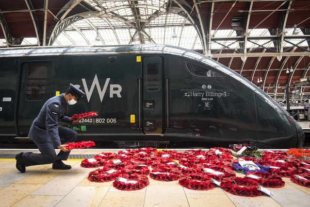 """Military personnel carry poppy wreaths at Paddington Station in London, for """"Poppies to Paddington"""" which is transporting memorial wreaths from around the UK on Great Western Railway train services into London Paddington on November 11, 2020. Wreaths are being laid around the station's war memorial for the two minutes silence to remember the war dead on Armistice Day. (Photo by Victoria Jones/PA Images via Getty Images)"""