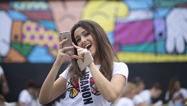In this Sunday, January 11, 2015 file photo, Miss Lebanon, Saly Greige, poses for photos after she painted on a wall in Miami's Wynwood area. (Photo by J. Pat Carter/AP Photo)