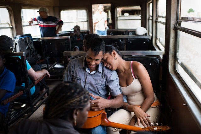 Les Daniel Manso, 22, sits with a guitar on his lap as his girlfriend, Glisveth Gonzalez, 15, right, rests her head on his shoulder. They are taking the electric train to Havana on March 30, 2015. About 30 miles east of Havana lies the now defunct sugar mill town of Camilo Cienfuegos which was built by the famous American chocolatier, Milton Hershey, and was originally named Hershey. The town grew up around a giant sugar mill and featured American style amenities in Cuba. (Photo by Sarah L. Voisin/The Washington Post)