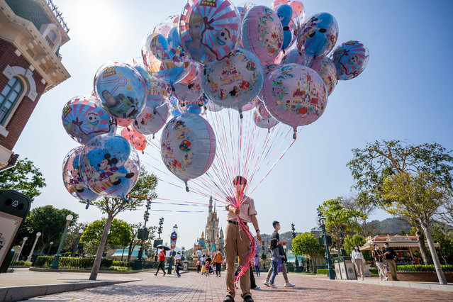 A Hong Kong Disneyland Resort employee sells balloons to victors during the reopening of the resort on February 19, 2021. The Hong Kong Disneyland Resort reopens its door to visors as the city's government has relaxed the lockdown restrictions as the infection rate of the Covid-19 coronavirus has reduced significantly in recent days. (Photo by Geovien So/SOPA Images/Rex Features/Shutterstock)