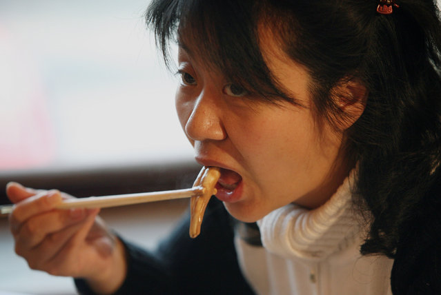 "A Chinese woman eats from an ox and dog pen*s dish at the Guolizhuang ""strength in the pot"" pen*s restaurant in China's capital Beijing March 3, 2006. The restaurant offers more than 30 types of animal penises served in a Chinese hotpot style. According to the theory of traditional Chinese medicine, the pen*s of certain animals is full of nutrients which brings men energy. And because it contains gelatine albumen, it is said to have excellent cosmetic effects for women, especially beneficial for the skin. (Photo by Reinhard Krause/Reuters)"